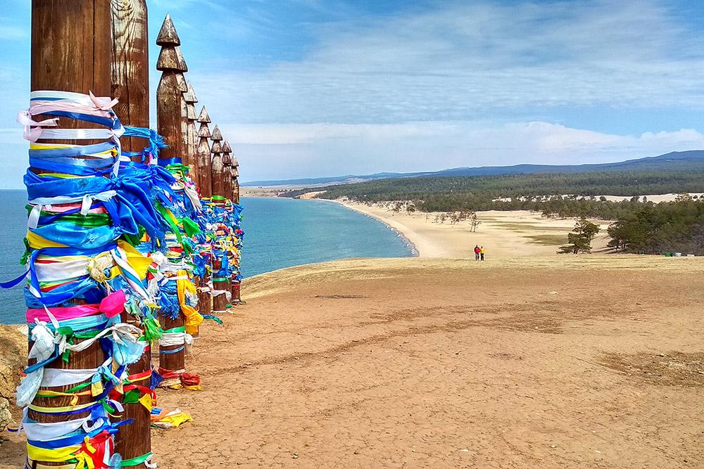 Молитвенные столбы Сэргэ и вид на пляж. По легенде, столбы нельзя демонтировать, они должны разрушиться сами. Оставить подвязку может каждый
